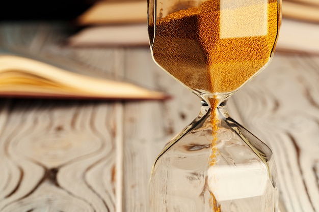 Sandglass on wooden table with opened book