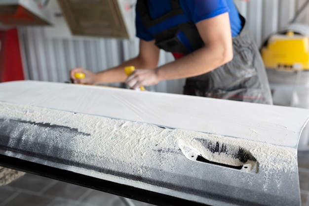 塗装前に、サービスステーションで車を紙やすりで磨いて磨く