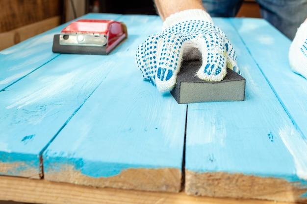 研磨スポンジ木製塗装青い木製テーブルでサンディング