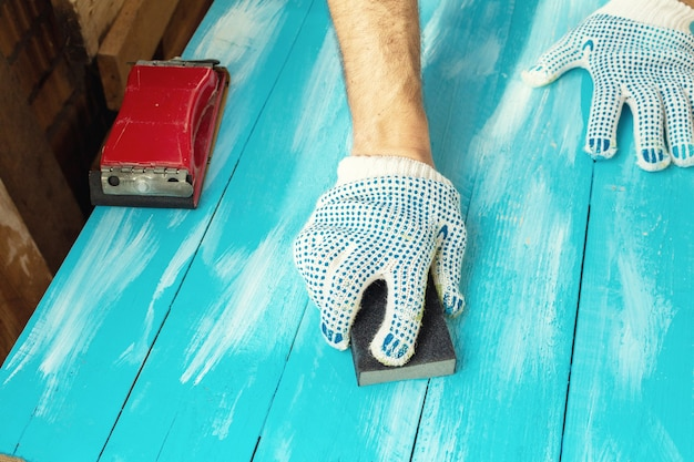 Sanding with abrasives in a hand in glove
