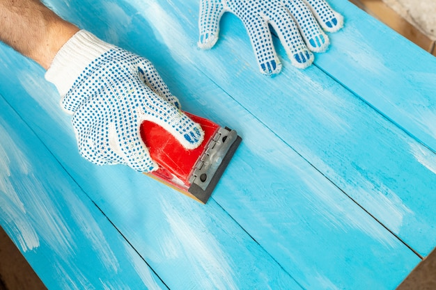 Sanding with abrasives in a hand sanding sponges painted blue wooden table background close up