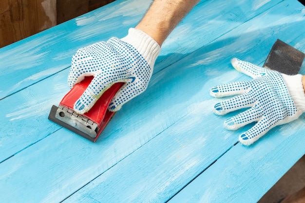 Sanding with abrasives in a hand wooden painted blue wooden table