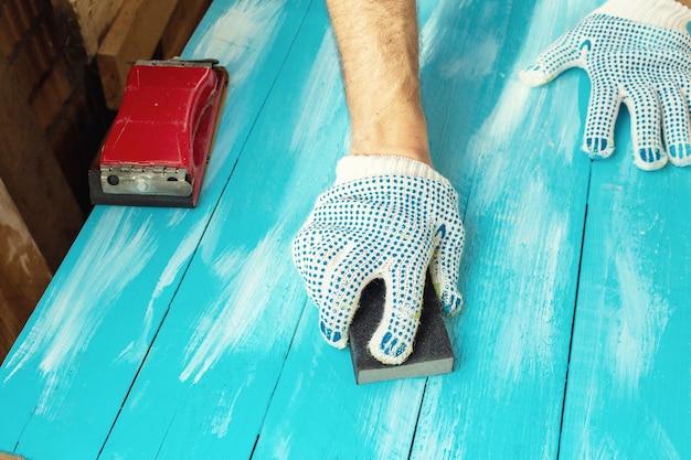 手袋をはめて研磨剤でサンディング