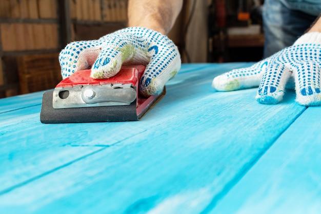 손에 연마재로 샌딩 푸른 나무 테이블 배경 그린