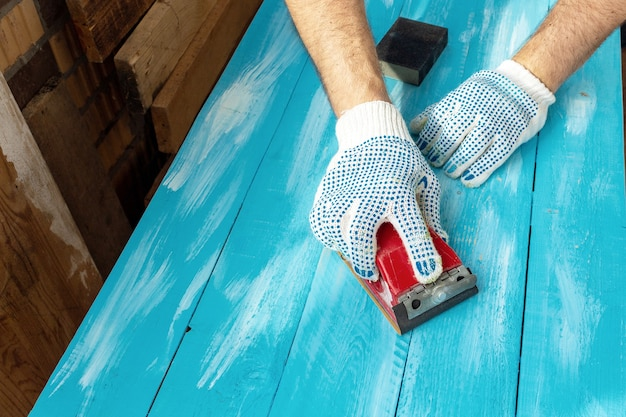 Sanding with abrasives on a painted blue wooden table