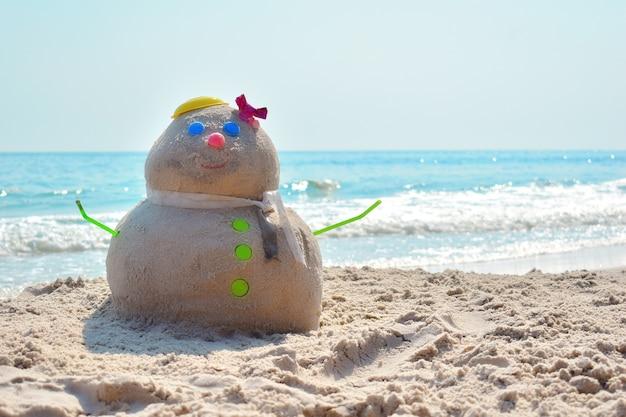 サンドマン。熱帯の新年。海でのクリスマス。海岸の楽しい砂図。海岸の砂で作られた雪だるま。島の新年あけましておめでとうございます。