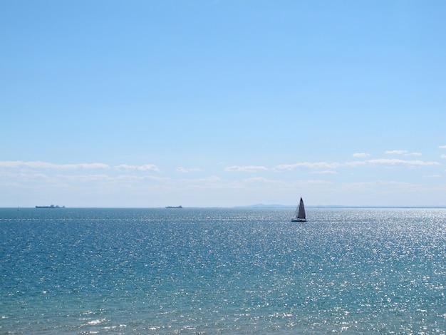 輝く海の水の景色はsandringhamビーチで青い空にヨットがあります。