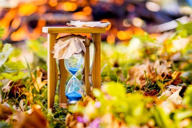 晴天の炉床にある秋の森の砂時計。秋の時間