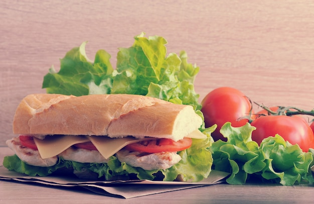 Sandwich baguette with chicken breast, cheese and tomatoes