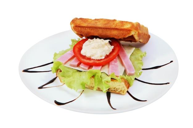 溶けたチーズ、ハム、トマトのリングレット、白い背景の上の孤立した画像とサンドイッチベルギーワッフル。