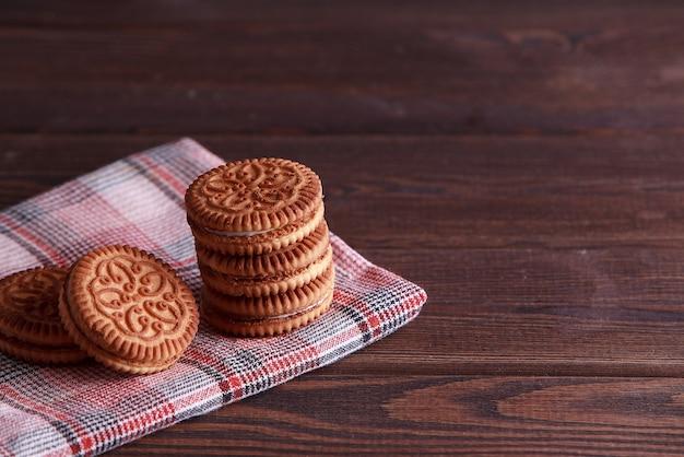 サンドイッチビスケット、クリームビスケット、木製テーブルにクリームを詰めたクッキー