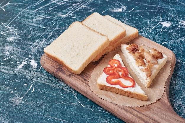 青いテーブルの上の木の板のサンドイッチパン。