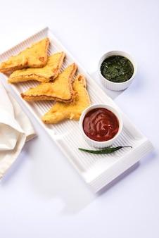 Хлеб-сэндвич пакора или пакода (треугольная форма) подается с томатным кетчупом, чатни, зеленым чили и ломтиками лука. популярная индийская закуска к чаепитию. выборочный фокус