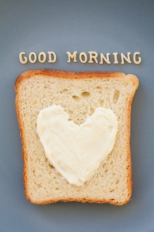 Sandwich for breakfast in the form of heart with cheese on a blue plate inscription good morning