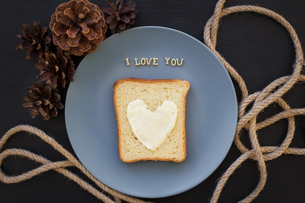 Sandwich for breakfast in form of heart with cheese on a blue plate