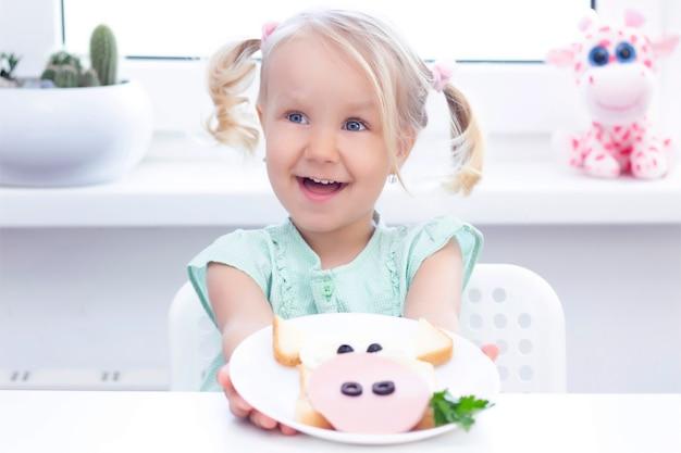 サンドイッチ牛。子供の女の子の手には白い皿があります。