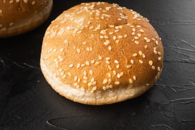 Sandwich bun with sesame seeds set, on black stone table