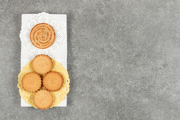 샌드위치 쿠키와 흰색 접시에 참 깨와 비스킷