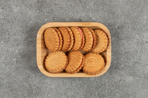 Печенье-сэндвич с кремом на деревянной тарелке