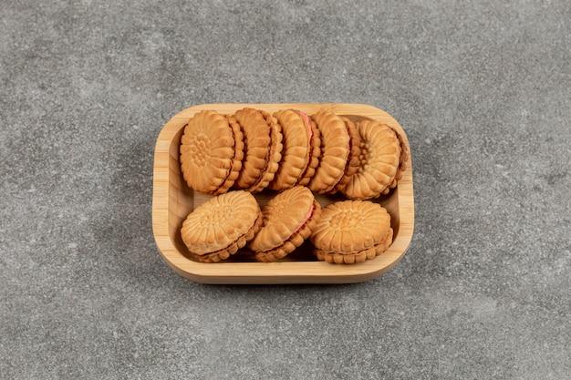 Biscotti del panino ripieni di crema sul piatto di legno
