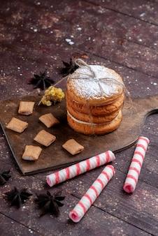 Biscotti sandwich con panna insieme a caramelle stick sulla scrivania marrone