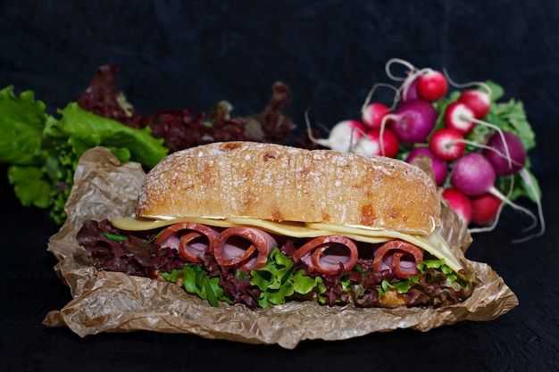 Sandwich of crispy ciabatta with ham, cheese and lettuce leaves.