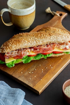 A sandwich of dark bread with salad, bacon, tomatoes and cheese. breakfast. fast food.
