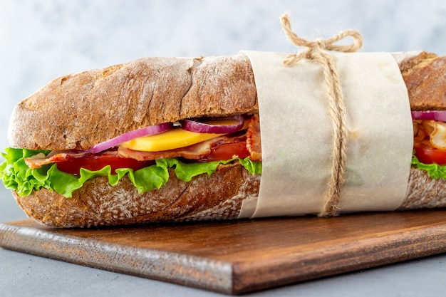 Sandwich of dark bread with salad, bacon, tomatoes, cheese and onions. breakfast. fast food.
