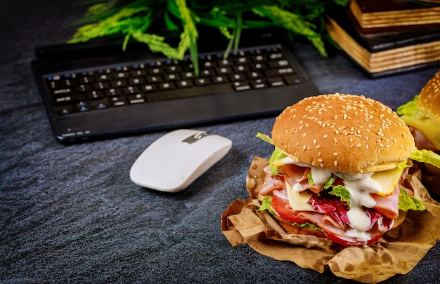 Sandwich on dark desk with keyboard, mouse and books