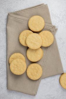 Сэндвич двойное печенье с белой кремовой начинкой с бежевым полотенцем на светло-серой бетонной поверхности.