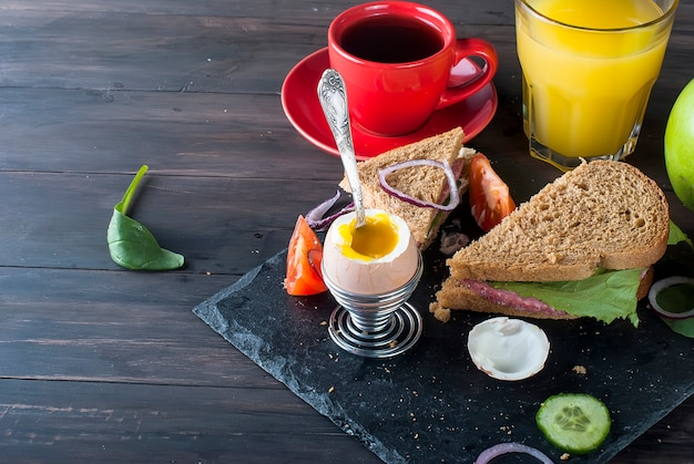 Sandwich, egg, cup coffe  and glass of juice for breakfast