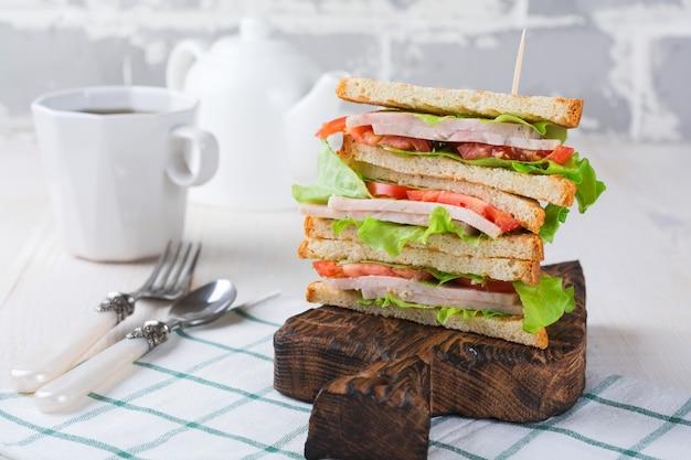 Сэндвич на завтрак с фаршированными помидорами, ветчиной и салатом на светлой деревянной поверхности. выборочный фокус.