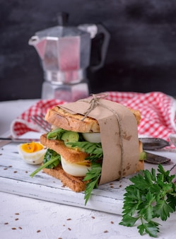 Sandwich of french toast and lettuce leaves and boiled egg, a vegetarian food wrapped in paper on a white wooden board