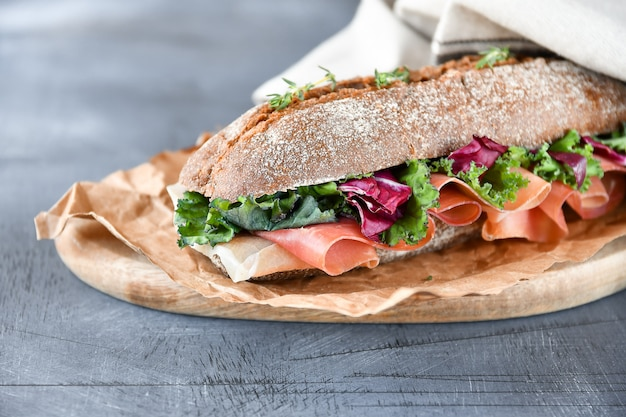 Sandwich from a cereal baguette  prosciutto, lettuce, kale on a gray background