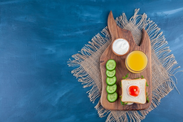 Sandwich, a glass of juice , bowl of cheese and sliced cucumber on a cutting board , on the blue background.