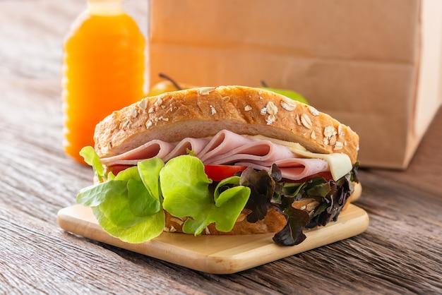 サンドイッチハムとチーズ、トマト、レタスと全粒粉パンのトースト。オレンジジュースとリンゴと茶色の紙のランチ。