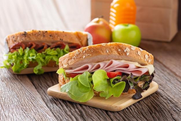 サンドイッチハムとチーズ、トマト、レタスと全粒粉パンをサラミサンドイッチで焼いたもの。オレンジジュースとリンゴと茶色の紙のランチ。