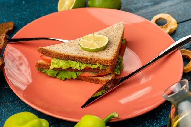 Бутерброд внутри тарелки вместе с зеленым болгарским перцем и лимоном на синем