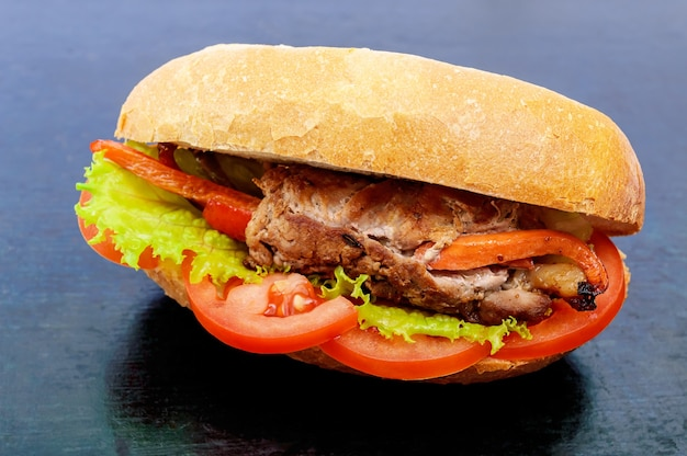 Sandwich meat rolls with vegetables in a bun with tomato and lettuce leaves