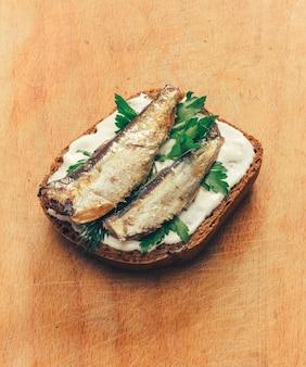 Сэндвич из консервированной шпроты на хлебе с майонезом и петрушкой