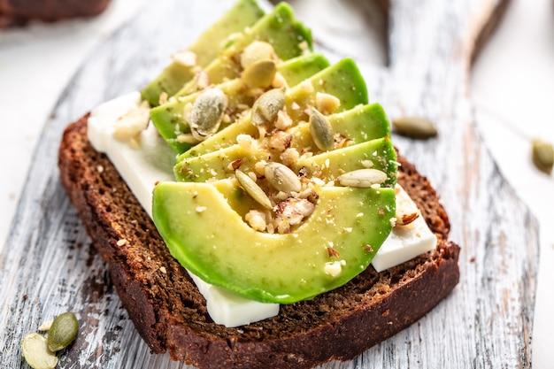 아침 또는 점심으로 아보카도와 염소 치즈를 곁들인 호밀 빵 샌드위치
