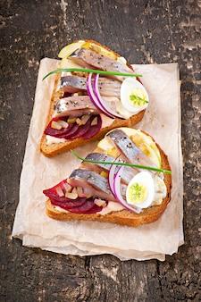 Бутерброд из ржаного хлеба с сельдью, свеклой, луком и яйцом
