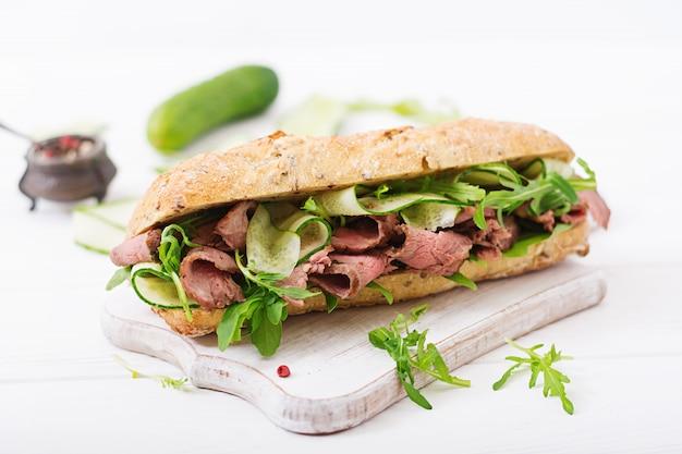 ローストビーフ、キュウリ、ルッコラの全粒小麦パンのサンドイッチ。