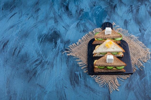 青いテーブルの黄麻布ナプキンのまな板のサンドイッチ。