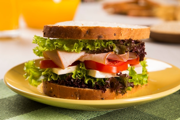 七面鳥の胸肉、トマト、レタス、チーズをテーブルに置いた白いプレートのサンドイッチ