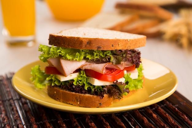 七面鳥の胸肉、トマト、レタス、白いチーズをテーブルに置いた白いプレートのサンドイッチ