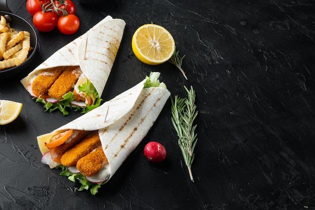 검은 배경에 생선 손가락, 치즈, 야채 세트가 있는 샌드위치 롤, 카피스페이스 및 텍스트 공간