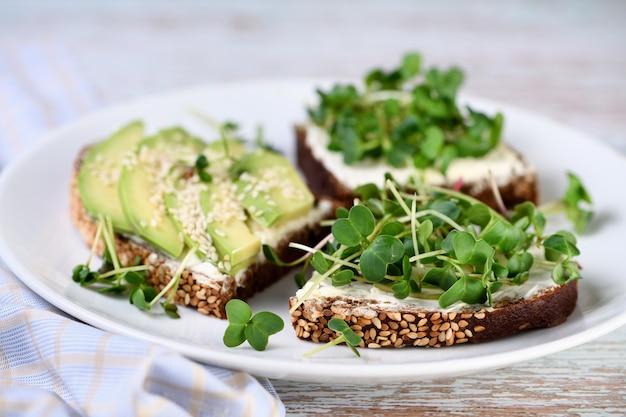 Сэндвич из ржаного хлеба с хлопьями, сливочным сыром, авокадо и проросшими ростками редиса (микрозелень)