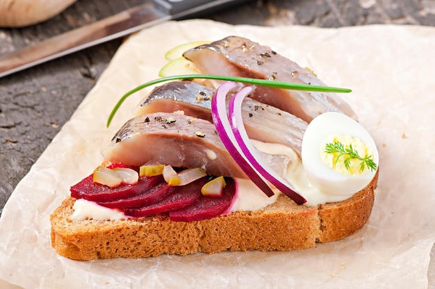Sandwich of rye bread with herring, beets, onions and egg