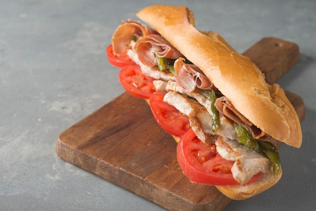 Sandwich serranito typical in andalusia with ham, gren pepper and grilled pork loin